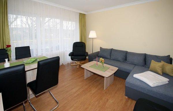 Wohnzimmer mit Schlafcouch, Essplatz und Flat-TV sowie Balkon