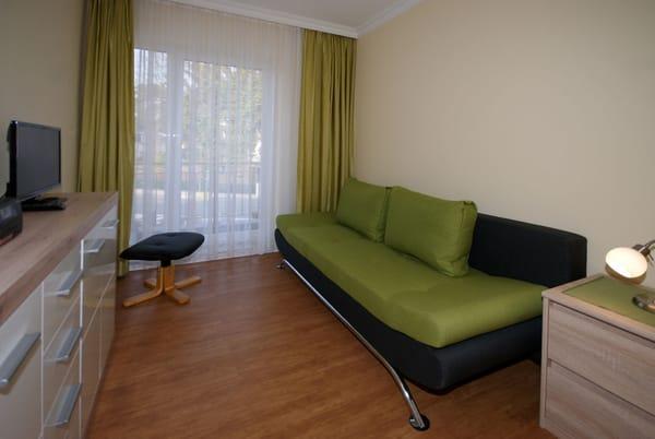 Wohnzimmer mit Flat-TV und Schlafcouch, frz. Balkon