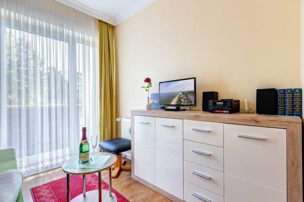 Wohnzimmer mit Flat-TV, Stereoanlage und frz. Balkon