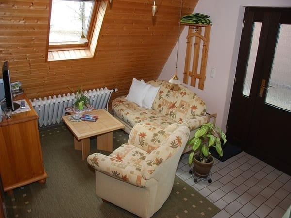 Wohnbereich mit gemütlichem Recamiere und Sessel sowie Flachbild-TV mit Sat-Reciver, Radio mit CD, Spiele- und Büchersammlung