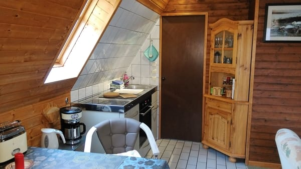 Essplatz und Miniküche mit zwei Herdplatten, Backofen, Kühlschrank, Wasserkocher, Toaster, Kaffeemaschine, sowie Zubehör wie Küchenhandtücher, Küchenrolle, Spülmittel usw.