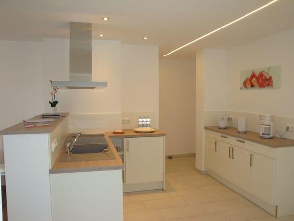 Küche mit Geschirrrspüler, Ablufthaube, Ceranherd, Kühlschrank mit Gefrierfach, Toaster, Kaffeemaschine und Wasserkocher