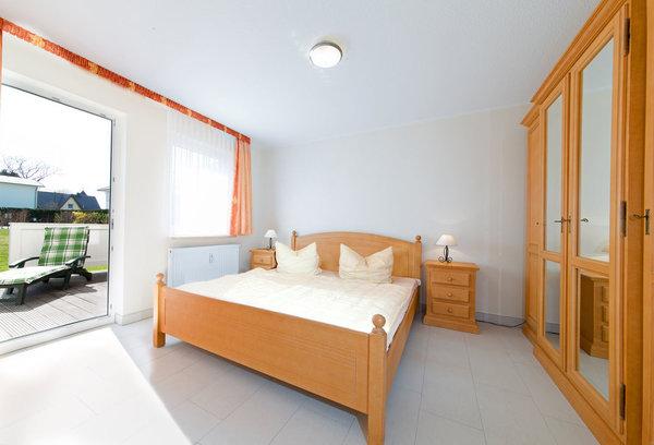 Schlafzimmer mit geöffneter Terrassentür. Ein Fernseher ist fest an der Wand zum Wohnzimmer montiert.