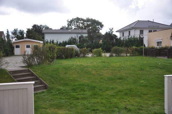 Blick von der Terrasse in den Garten. Hinten links ist das Fahrradgebäude zu sehen.