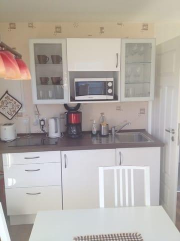 Gut ausgestattete Küche mit Kühlschrank, Mikrowelle, Kaffeemaschine und vielem mehr