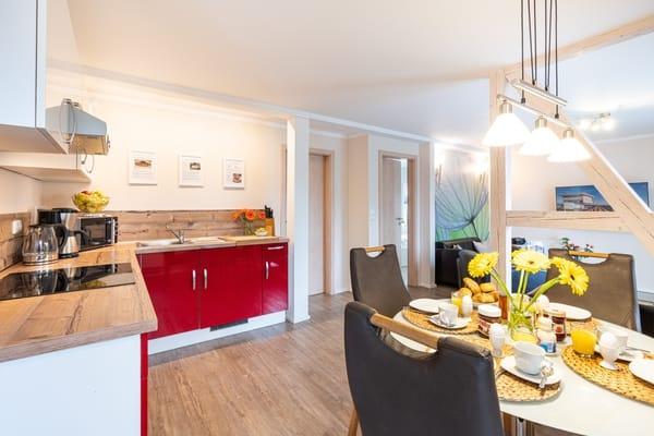 Die integrierte Küchenzeile mit Essecke für 4 Personen lässt keine Wünsche offen: Kühlschrank mit Gefrierfach, Ceran-Kochfeld, Backofen, Geschirrspülmaschine, Kaffeemaschine, uvm.