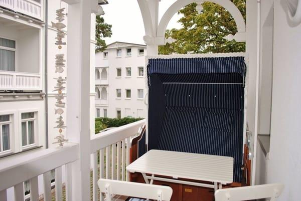 Balkon in Bäderarchitektur mit Strandkorb und Sitzgelegenheiten