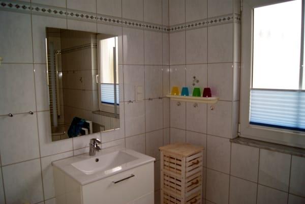 Das Bad mit Wanne und Fenster.