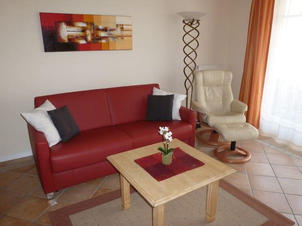 gemütliches Wohnzimmer zum Entspannen mit komfortabler Leder-Schlafcouch und Relaxsessel