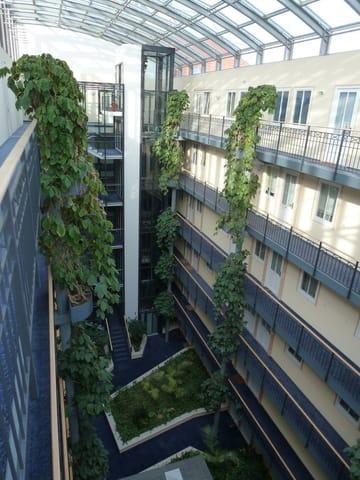 lichtdurchflutetes, bepflanztes Atrium mit zwei gläsernen Aufzügen von der Tiefgarage in die einzelnen Etagen