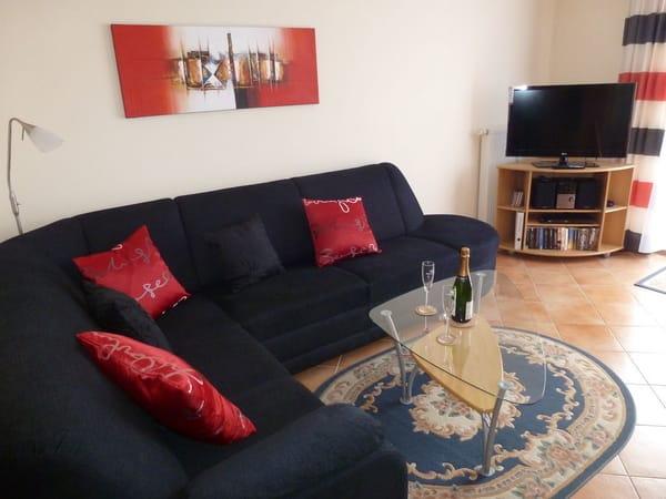 Wohnzimmer mit gemütlicher Sofaecke und modernem 90 cm LED-Fernseher
