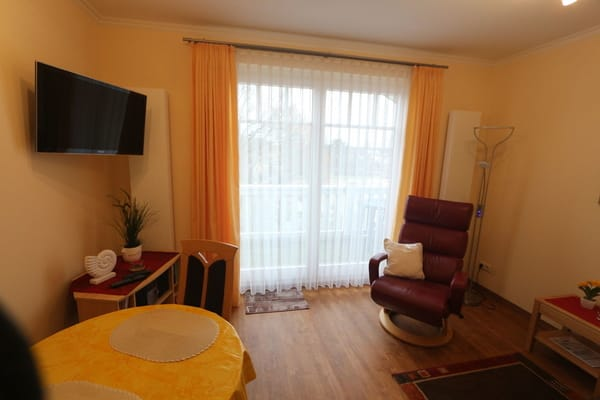 gemütliches Wohnzimmer mit Relaxsessel und LED-Fernseher