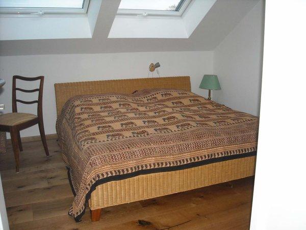 kleineres Schlafzimmer mit Doppelbett auf Eiche