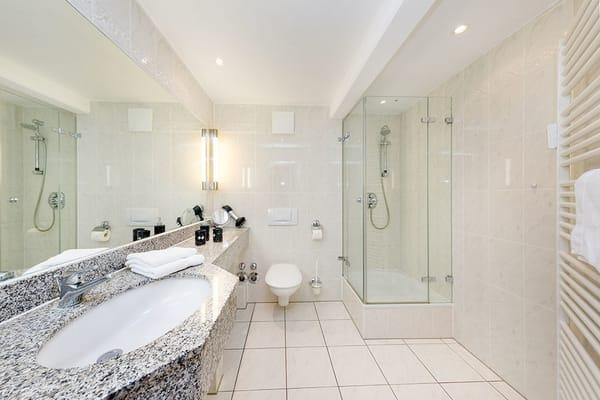 Hier ein Blick in das große Bad mit Echtglasdusche, Fön und WC.