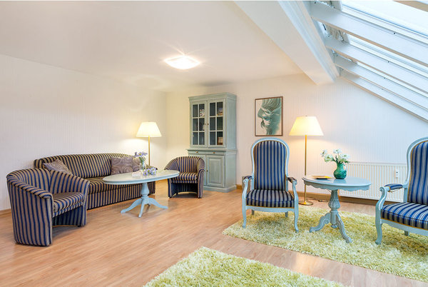 Auf der Couch kann für 1 Person aufgebettet werden. Die Fenster sind mit Plissees ausgestattet. Das Wohnzimmer schaut nach Nordosten auf die Ostsee.