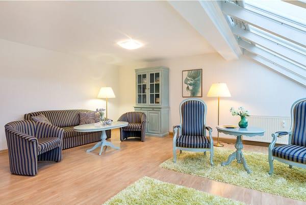 Die Fenster sind mit Plissees ausgestattet. Das Wohnzimmer schaut nach Nordosten auf die Ostsee. Die Couch hat keine Schlaffunktion.
