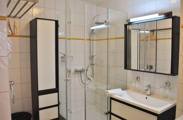 modernes Bad mit Dusche und Handtuchwärmer