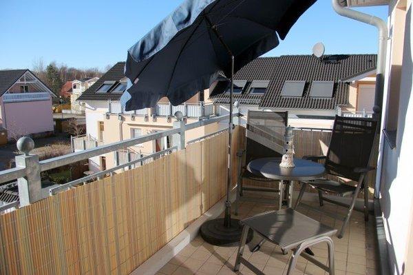 Balkon mit Balkonmöbeln und Sonnenschirm