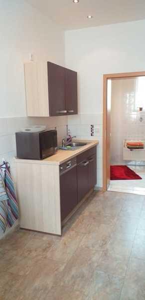 Küche mit Spüle und Geschirrspüler, Einblick ins Bad