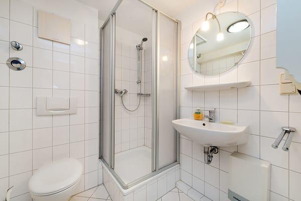 Das Bad bietet Dusche, WC und Waschbecken.