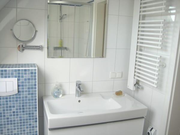 Bad mit Dusche und Möbelwaschtisch, der viel Stauraum bietet.