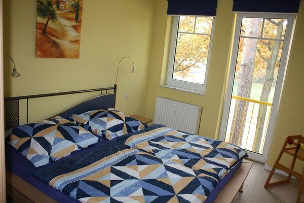 Schlafzimmer mit Doppelbett und großem Kleiderschrank. Laminatfussboden