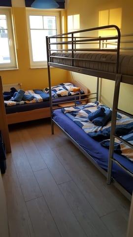Kinderzimmer mit einem Etagenbett und einem Einzelbettund kleinem Schrank mit einer kleinen Auswahl an Spielsachen und Kinderbüchern.