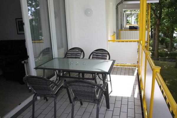 Balkon mit 4 Sitzgelegenheiten. Sitzauflagen sind vorhanden, ebenso wie ein Wäscheständer.