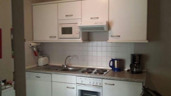 Küchenzeile, voll ausgestattet mit Mikrowelle, Geschirrspüler, Herd mit 4 Kochplatten, Backofen, Kühlschrank mit Gefrierfach, Kaffemaschine, Wasserkocher, Toaster und ausreichend Geschirr und Besteck