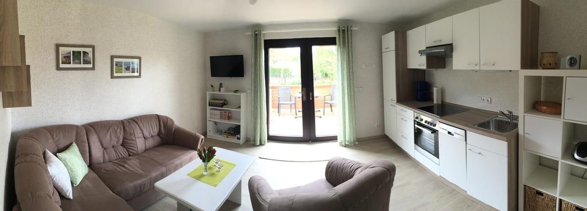 Wohnbereich mit offener Küche und Blick auf die Terrasse