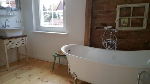 Bad mit Holzfußboden, freistehender Wanne, großer Dusche, Fenster