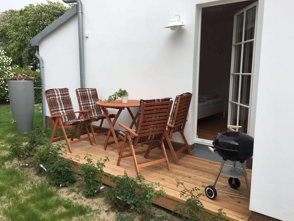 Terrasse mit Sitzmöbeln, Grill, Wildrosenhecke