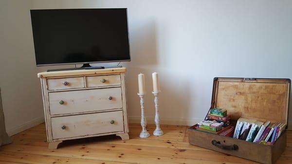 Wohnzimmer mit Bücher- und Spielekoffer, großem TV