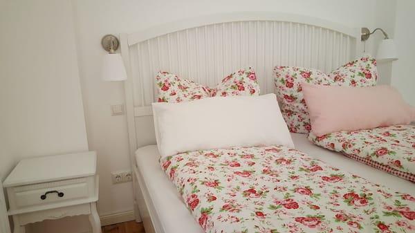 Schlafzimmer mit großem Doppelbett, TV und Zugang zur Terrasse