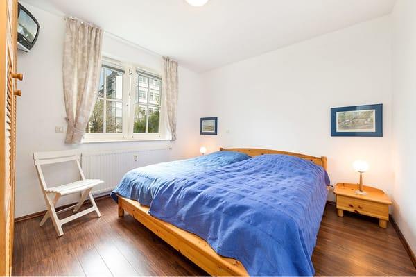 Das Schlafzimmer mit Doppelbett und Kleiderschrank, hat ein 2. TV-Gerät und einen Außenrolladen am Fenster.