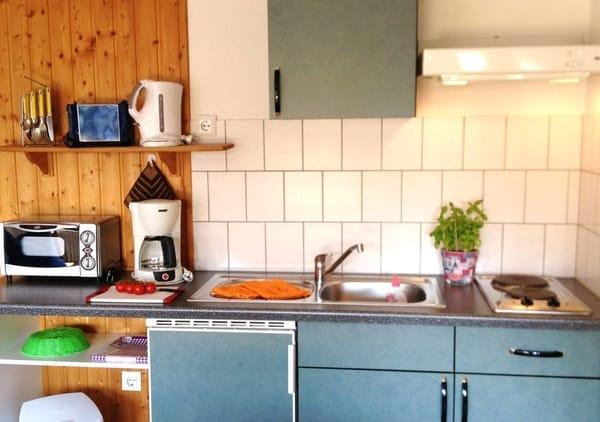 Küchenzeile mit 2-Platten-Herd, Wasserkocher, Kaffeemaschine, Toaster und Miniofen