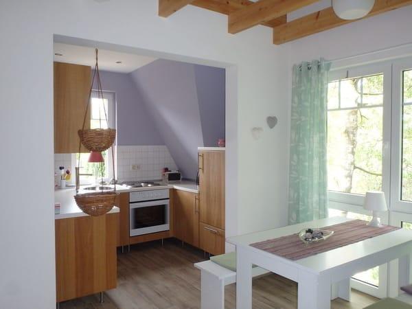 Essbereich und offene Küche mit Kühlschrank, Herd, Backofen, Geschirrspüler, Caffissimo-Maschine