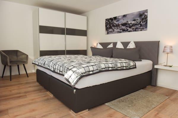Schlafzimmer mit Boxspringbett, Kleiderschrank und Sessel