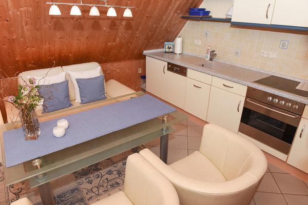 Wohnbereich mit Couch und Essplatz / Küchenzeile (mit Spüle, Geschirrspüler, Cerankochfeld und Backofen)