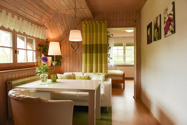 Wohnbereich mit Couch, Tisch & Sessel (Blick in den Schlafbereich)
