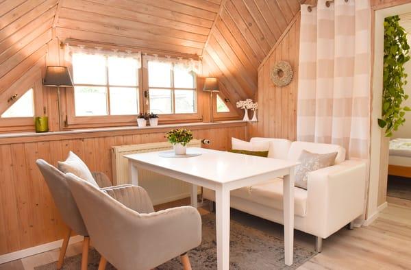 Wohnbereich mit Couch, Tisch & 2 Stühlen (Blick in den Schlafbereich)