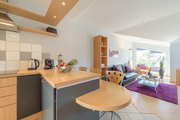 Das Wohnzimmer ist mit einem bodentiefen Fenster ausgestattet, die Relaxsessel davor bieten eine gute Möglichkeit für Entspannungen mit einem Buch oder einem Gläschen Wein.