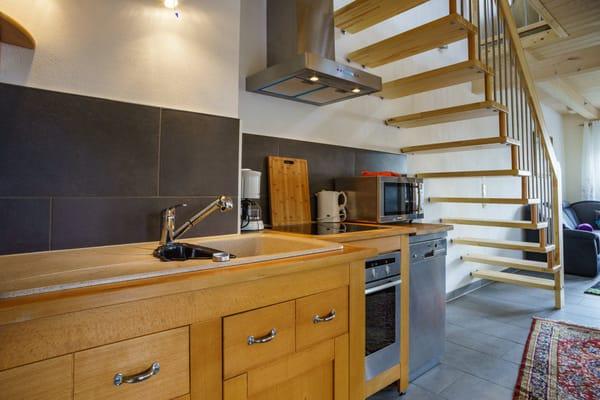 Einer offenen Küche mit Ceranfeld, Kühlschrank, Mikrowelle und Kaffeemaschine.