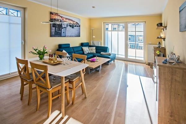 Ein bequemes Sofa, Flat TV sowie ein Esstisch für vier Personen laden zum Entspannen und geselligem Beisammensein im gemütlichen Wohn- und Essbereich ein.