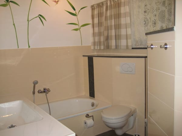 großes Bad mit Badewanne, barrierefreier Dusche und elegantem Waschtisch