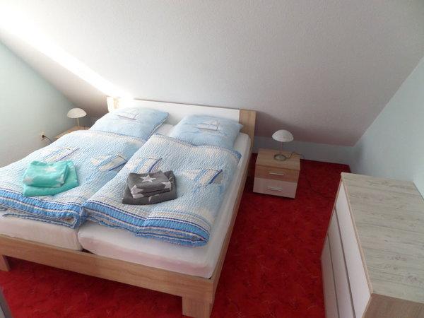 Schlafzimmer mit Doppelbett und Sideboard