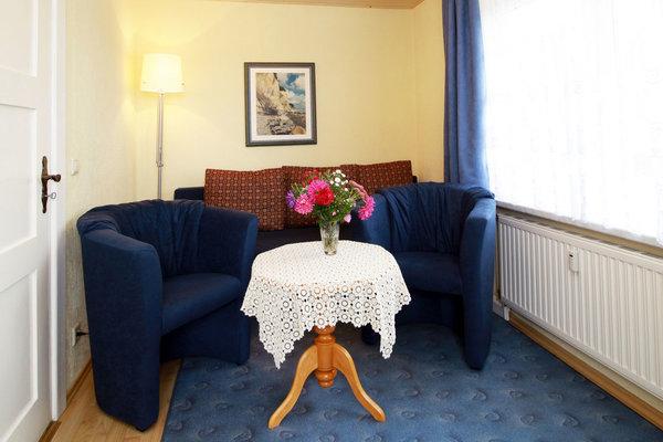 Wohnraum mit Couch, Sesseln und Flachbildschirm