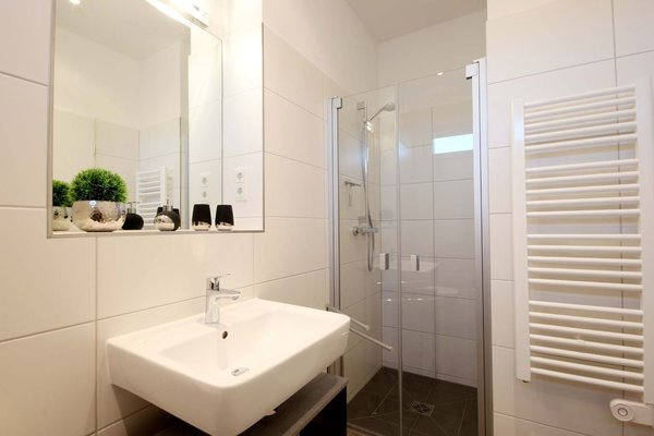 Tageslichtbad ist mit ebenerdiger Dusche, Waschtisch, Kosmetikspiegel, Fön und WC