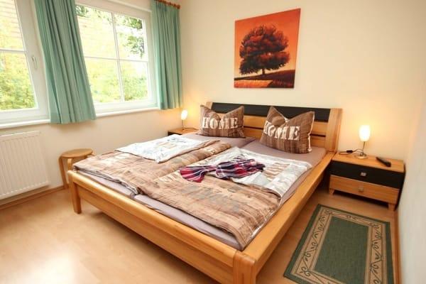 Schlafzimmer mit Verdunklungsstoffen, Doppelbett, geräumigem Kleiderschrank und einem weiteren Flachbild-TV