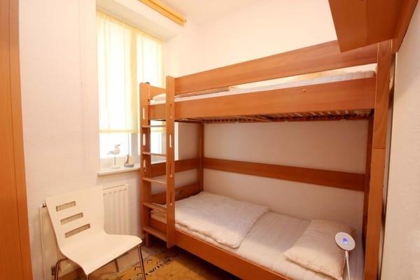 kleines Schlafzimmer mit Doppelstockbett und Fenster mit Brandschutzfunktion (kann nicht geöffnet werden)